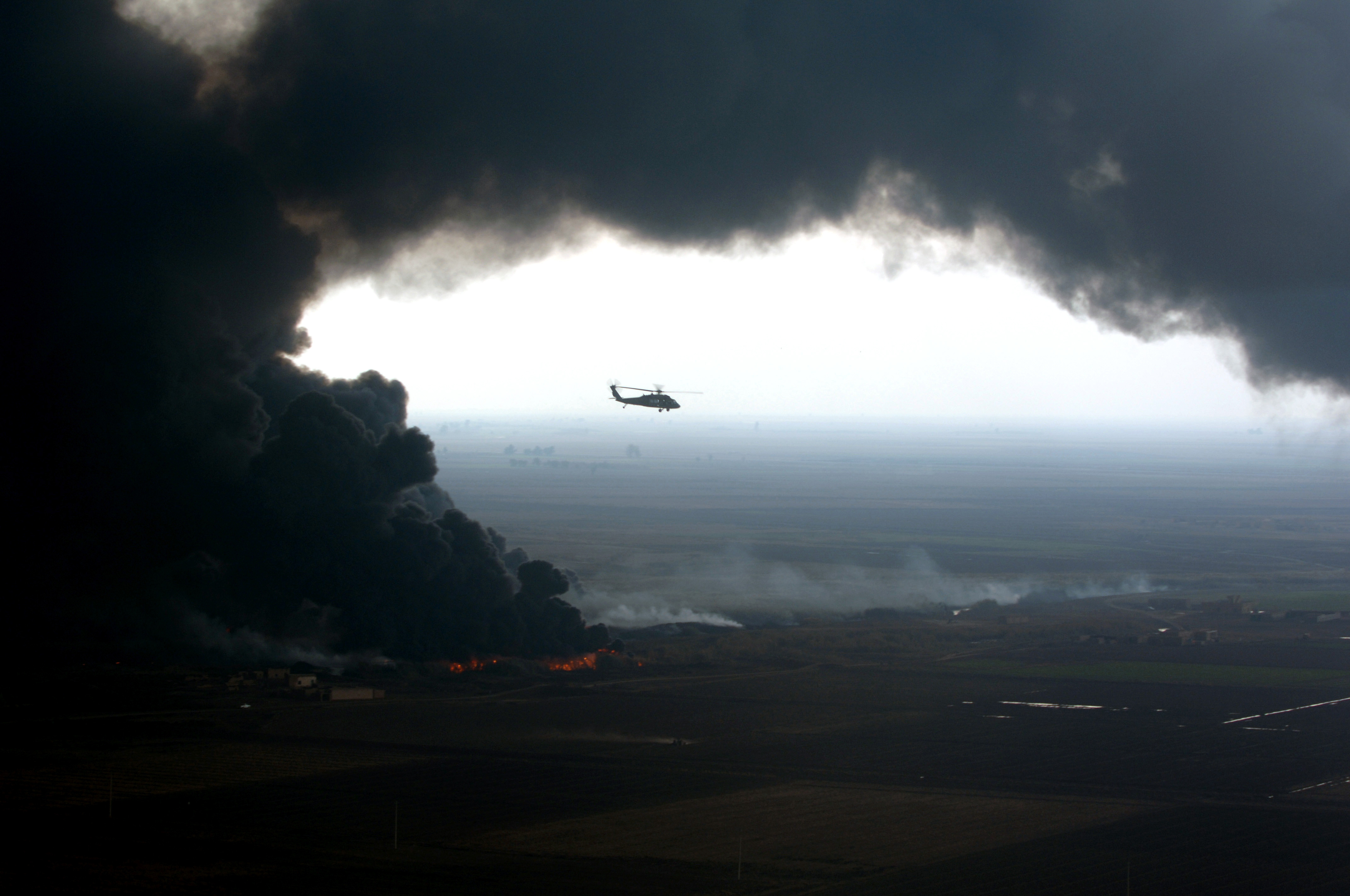 A plume of smoke surrounds a U.S. Army UH-60 Black Hawk helicopter as soldiers of the 101st Airborne Division conduct an aerial assessment of an oil pipeline fire outside Forward Operating Base McHenry, Iraq, on Dec. 27, 2005.  Elements of the 101st Airborne Division are deployed to Iraq from Fort Campbell, Ky.  DoD photo by Spc. Timothy Kingston, U.S. Army.  (Released)